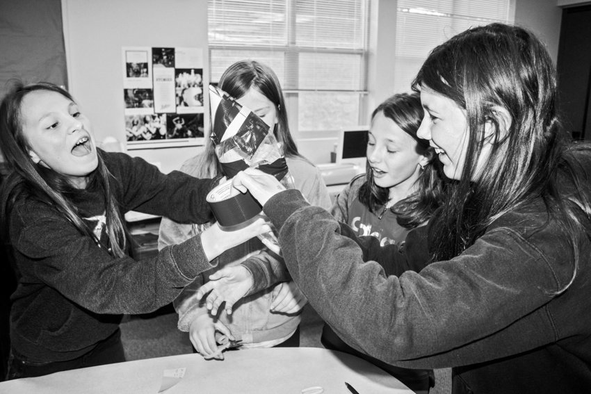 Chimacum Middle School students (from left) Sophia Lawson, Chloe Mouser, Mikiah Winter and Isabell Raymond become rambunctious as they tape their bottle rocket together. Photo by Kirk Boxleitner