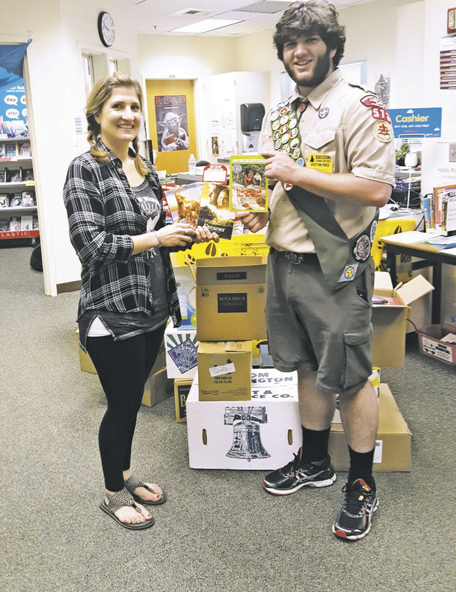 Eagle Scout Brandon Pizzini delivers 580 donated books to Quilcene School librarian Alicia Johnsen, appropriately enough, during Happy Camper Book Fair week. Photo by Viviann Kuehl