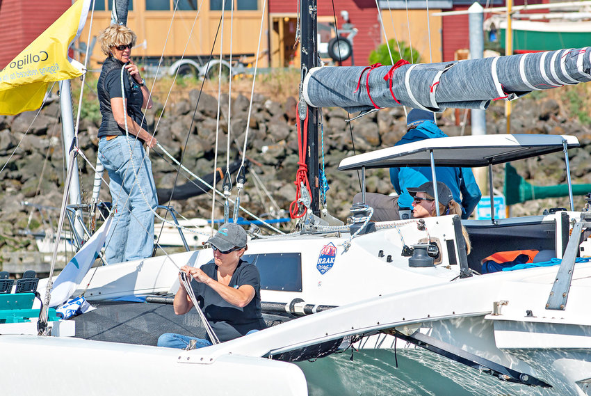 """Race to Alaska competitors (from left) Michelle Boroski, Stephanie Maheu and Stephanie York prepare their Corsair F-27 trimaran at the Point Hudson Marina on Tuesday, June 6. The women, along with Johanna Gabbard, are with the Ventura, California–based all-female """"Team Sistership."""" Boroski, the captain, said they completed the race last year and are trying to improve their time this year. They also raised $8,000 in Northwest Maritime scholarships for women and girls. In the blue jacket is Bob Downes with Brion Toss Yacht Riggers. Boroski lived in Port Townsend for 10 years prior to moving to Ventura and said the team was """"way more prepared than we were last year."""" Learn more at sistership.org. Photo by Chris Tucker"""