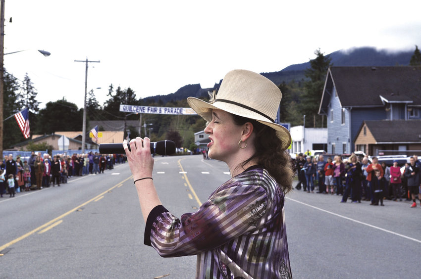 """Anne Gibson kicks off the 2016 Quilcene Fair and Parade by singing the national anthem to the attentive crowd lining both sides of U.S. Highway 101 in """"downtown"""" Quilcene. This year's fair is set for Sept. 16-17. File photo by Viviann Kuehl"""