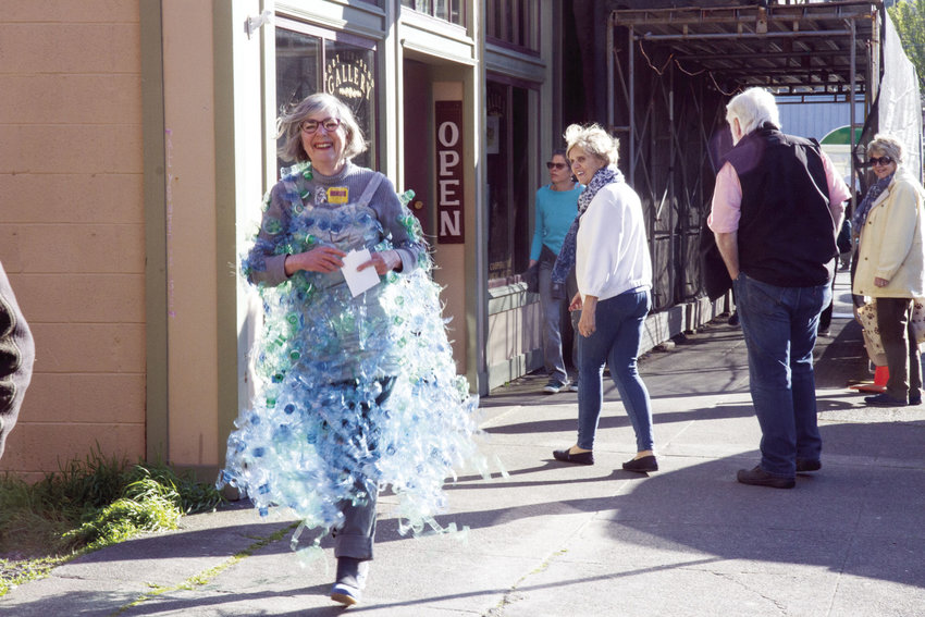 Judith Bird draws attention from onlookers as she walks down Water Street on May 6 in a wearable art creation made out of recycled plastic bottles. She was helping to promote the May 13 Port Townsend Wearable Arts show along with Teri Nomura and Margie McDonal. The annual show is a benefit for the Jefferson Community Foundation Fund for Women and Girls. See details, below. Photo by Katie Kowalski