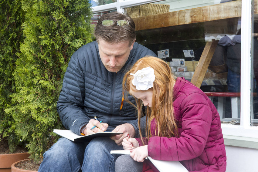 "Eric Kuzma (left) and his daughter, Anora, sketch at the Port Townsend Farmers Market on Saturday, April 29. Anora, who just turned 7, has been drawing ""since I was a baby,"" she said. Her sketchbook (below) was filled with art. The father-daughter team sat outside of Pane d'Amore to participate in a Port Townsend Urban Sketchers outing. Photos by Katie Kowalski"