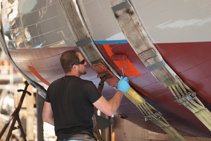 Charlie Duerr paints a small section of the Sea Beast's exterior that had been used for cribbing. The motor sailor was designed by Carl Chamberlain and built by the Northwest School of Wooden Boatbuilding's classes of 2014, 2015 and 2016.