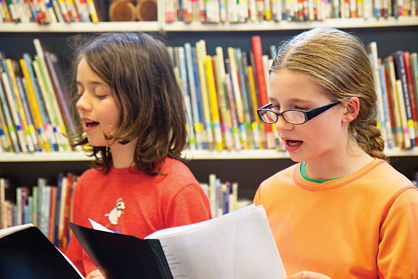 Charlotte Capel (left) and Mariel Price practice songs during an impromptu rehearsal May 3 of the Port Townsend Public Library Children's Choir, in preparation for a concert on Saturday, May 13. The library children's choir, under the direction of Phina Pipia, is set to perform at 2 p.m. at First Baptist Church. Photo by Katie Kowalski