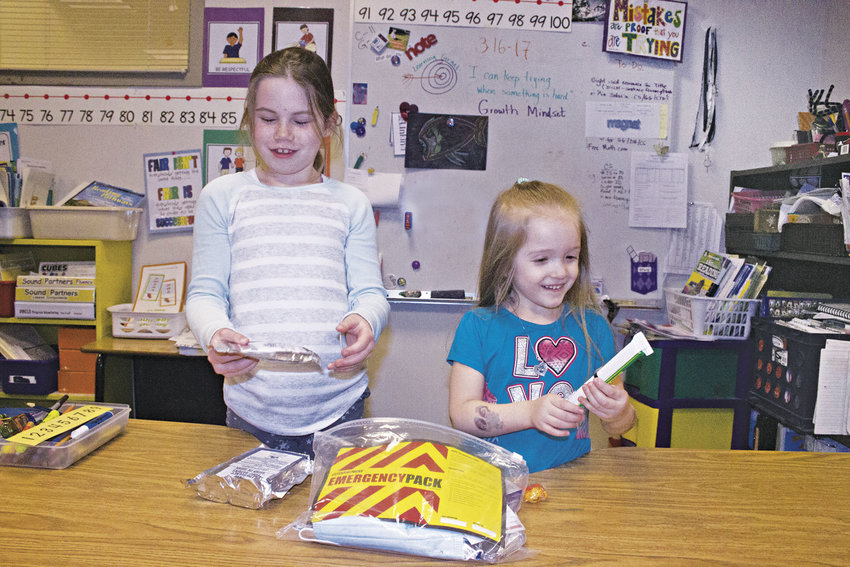 Chimacum Creek Primary School Gracee Laske, 7, and Kloe Enlow, 4, explore the contents of one of the school's emergency supply kits. Photo by Kirk Boxleitner