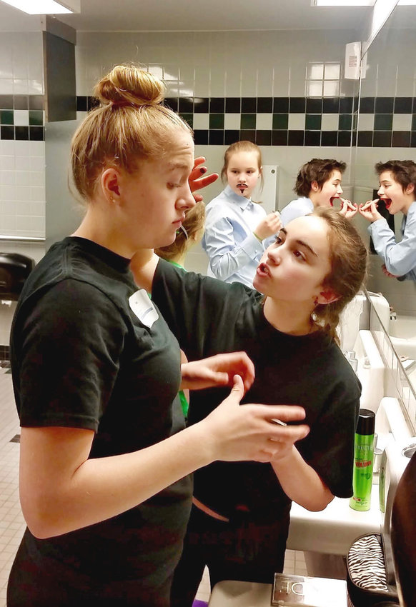 Destination Imagination competitor Esther Gleeman (right) helps teammate Ava Amos with her makeup. The students put on an eight-minute story presentation that combines science, humor, music and artistic design. Courtesy photo