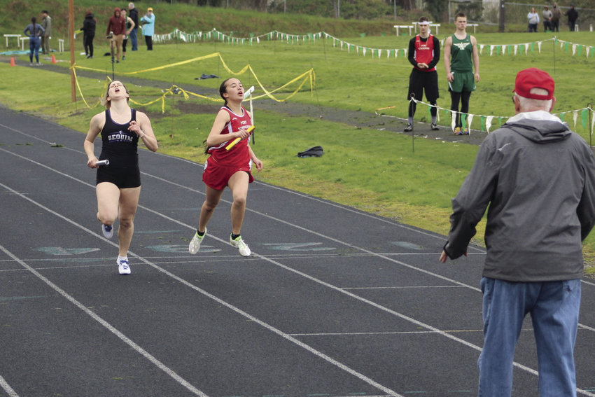 Anika Avelino, right, holds off Sequim in a tight 4-x-100 meter relay finish April 20. Photo courtesy Donna Winter