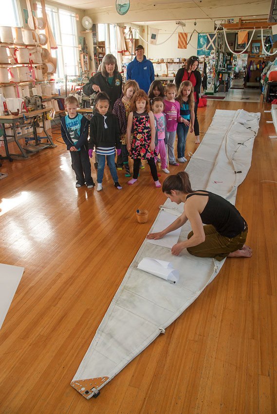 """Sails are wings,"" says Carol Hasse, owner of Port Townsend Sails (standing behind children, at left, in black jacket) as she shows a group of Grant Street Elementary first-graders a sail being repaired on April 11. Pictured (from left) are Tarrence W., Nyla R., Carol Hasse, Malia W., Hope Q., Naveah G., Sophia B., Lily R., Idalya S. and Ashley Quinn. Working on the sail is employee Erica Georgaklis. Photo by Chris Tucker"