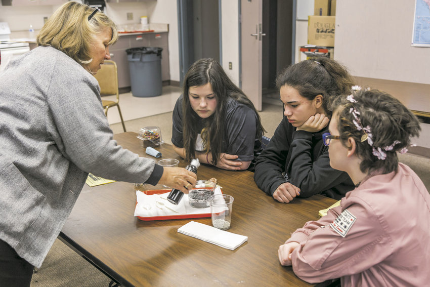 Laura Tucker of Jefferson County Public Health shares an oil-spill cleanup experiment with Chimacum Middle School students (from left) Jadeah Nordberg-Williams, Kyara Stallworth and Hope Aman. Photos courtesy of Mitchel Osborne Photography