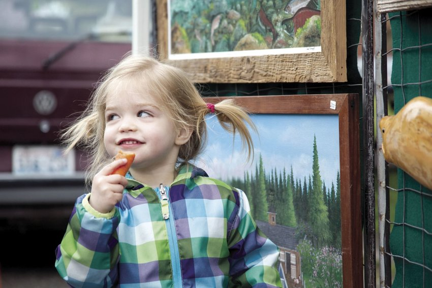 Locking eyes with her father, Coraline Force, 2, chews on a carrot while nearly touching art at the season opening of the Port Townsend Farmers Market on Saturday, April 1. For more pictures, see pages 8 and 9 of the printed edition.Photo by Lloyd Mullen