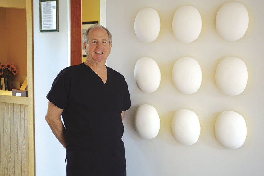 Port Townsend dentist Steven Scharf stands in front of a sculptural work by Port Townsend ceramist Anne Hirondelle in the waiting room of his Uptown clinic, where he has hosted the work of many artists over the years. Scharf has been named a Patron of the Arts by the Port Townsend Arts Commission. Courtesy photo