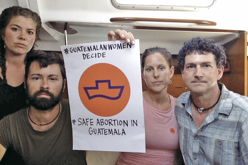 Merilee Nyland Evans (second from right) and Daniel Evans (far right) hold a poster in support of Women on Waves' mission of providing abortion services in Guatemala. Also pictured (at left) are crew members Alecia Ott and Seth Bearden. The Evanses, who are from Port Townsend, are expected to return home March 3. Courtesy photo
