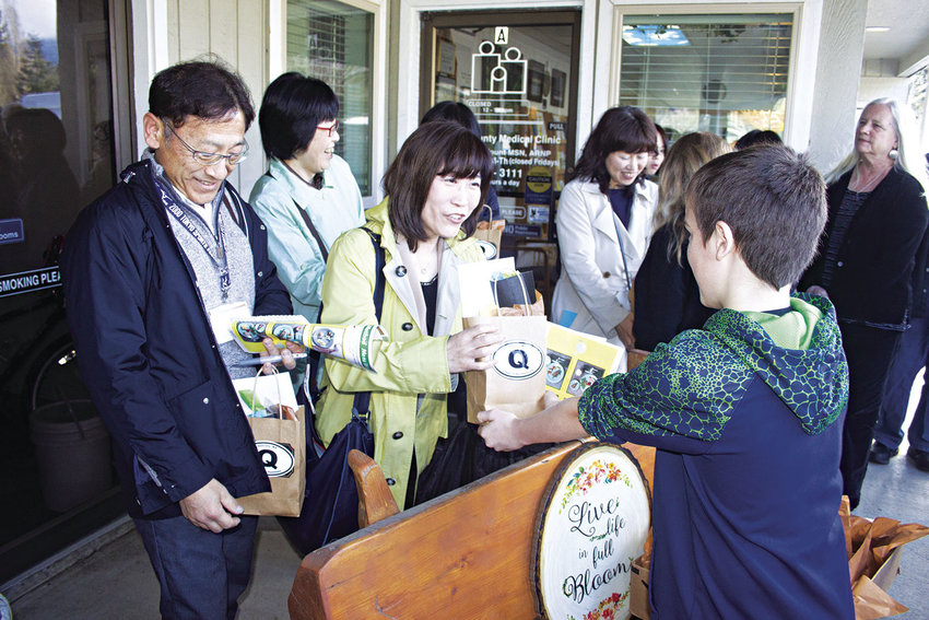 Ishikawa Prefectural Nursing University faculty members (from left) Noboru Hasegawa and Hisae Tsukada receive gifts from Quilcene sixth-grader Barron Williams at the South County Medical Clinic in Quilcene March 24. Photo by Kirk Boxleitner