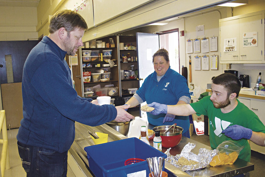 From left, state Rep. Mike Chapman, D-Port Angeles, samples the meals served by YMCA staff members Rowen DeLuna and Travis Spencer five days a week in Port Townsend. Photo by Kirk Boxleitner