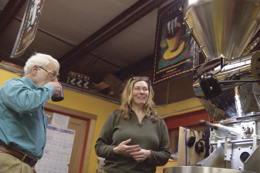 Earll Murman, left, listens as Sue Ohlson, co-owner of Sunrise Coffee in Port Townsend, explains the workings of a $100,000 coffee roaster, which Murman and other local investors helped her to purchase. The roaster also is helping to expand her business. Ohlson is scheduled to be one of the loan recipients to speak about LION (Local Investing Opportunities Network) on Saturday. Murman is a member of LION. Photo by Allison Arthur