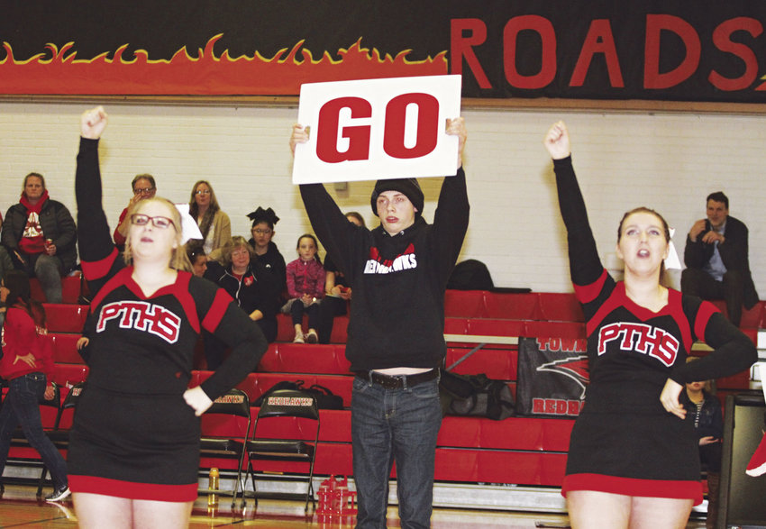 Nick Hamon, a Port Townsend High School senior who has autism, has stepped up this year to become the manager of the cheerleading team, and now participates with the cheerleaders by holding a sign during an on-court routine. Photo by Patrick Sullivan