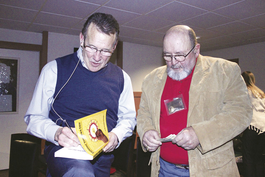 "Mac Macdonald signs a copy of his book, ""Lighting Your Own Fuse,"" for Jefferson County Toastmaster Jeffrey Hartman. Photo by Kirk Boxleitner"