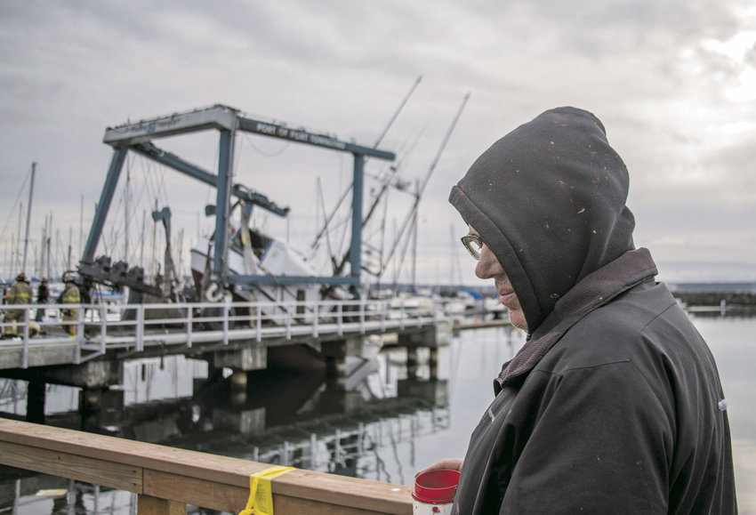 Commercial fisherman Mike Deach of Lopez Island watches as plans are made to recover his 60-foot, 75-ton boat, left partially suspended when the Port of Port Townsend's 75-ton boat hoist failed. Photo by Lloyd Mullen