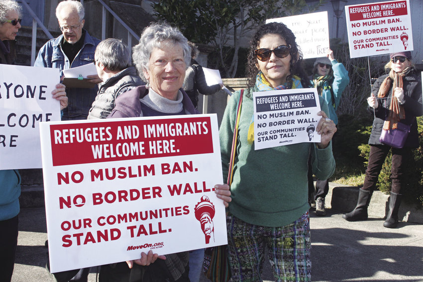 Judy D'Amore, left, and Liseth Marroquin, the latter a legal resident who hails from Guatemala, stand together against deportations at the office of the U.S. Postal Service in Port Townsend Feb. 13. Photo by Kirk Boxleitner