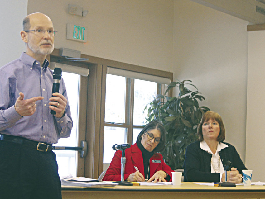 Jefferson County Administrator Philip Morley (far left) explains the details of a settlement agreement between the county and Port Ludlow Associates (PLA), as County Commissioner Kathleen Kler (center) and Diana Smeland, PLA president (far right), listen. Photo by Allison Arthur