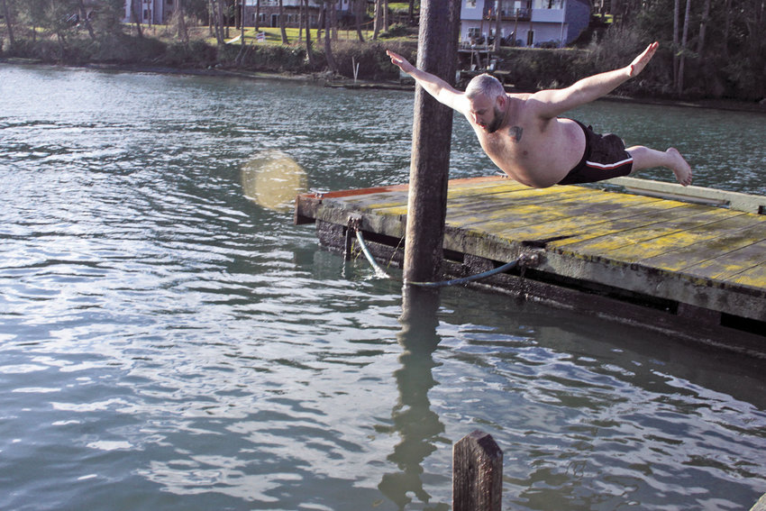 Zach Devos of Portland, Oregon, executes a perfect belly-flop off the dock at the Nordland General Store for this year's Polar Bear Dip. Photo Kirk Boxleitner