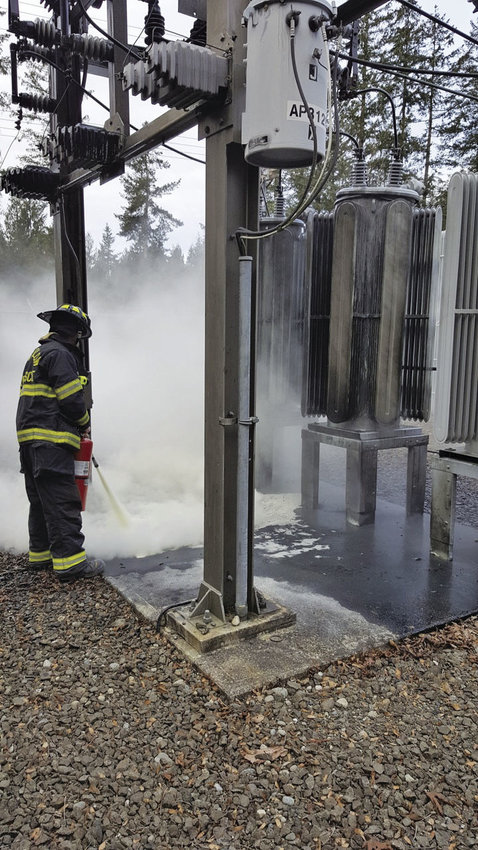 Port Ludlow Fire & Rescue firefighter Justin Sly works to extinguish flames after a voltage regulator at a Port Ludlow PUD substation exploded Jan. 11. Photo courtesy of Keppie Keplinger