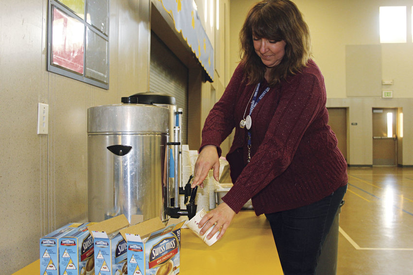 RaeLynn Whiteside, a paraeducator at Chimacum Middle School, pours hot cocoa for herself as she waits to serve those affected by the Port Ludlow power outage at the school's officially designated warming station Jan. 11. Photo by Kirk Boxleitner
