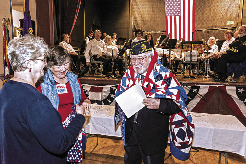 Andy Okinczyc, Legion post commander, receives a quilt from Kathey Bates and Marilyn Bryant on Veterans Day, Nov. 11, 2016 during a ceremony at the American Legion Marvin G. Shields Memorial Post 26. Quilts of Valor is hosting its National Sew Day on Saturday, Feb. 4 at the Legion. Courtesy photo