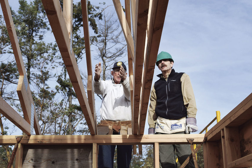 Volunteers Bob Young (left) and Bob Rewitzer discuss the nuts and bolts of building a roof during the Interfaith Group Build, which brought together volunteers of different faiths to help construct houses for Habitat for Humanity of East Jefferson County. Photo by Jay Syverson