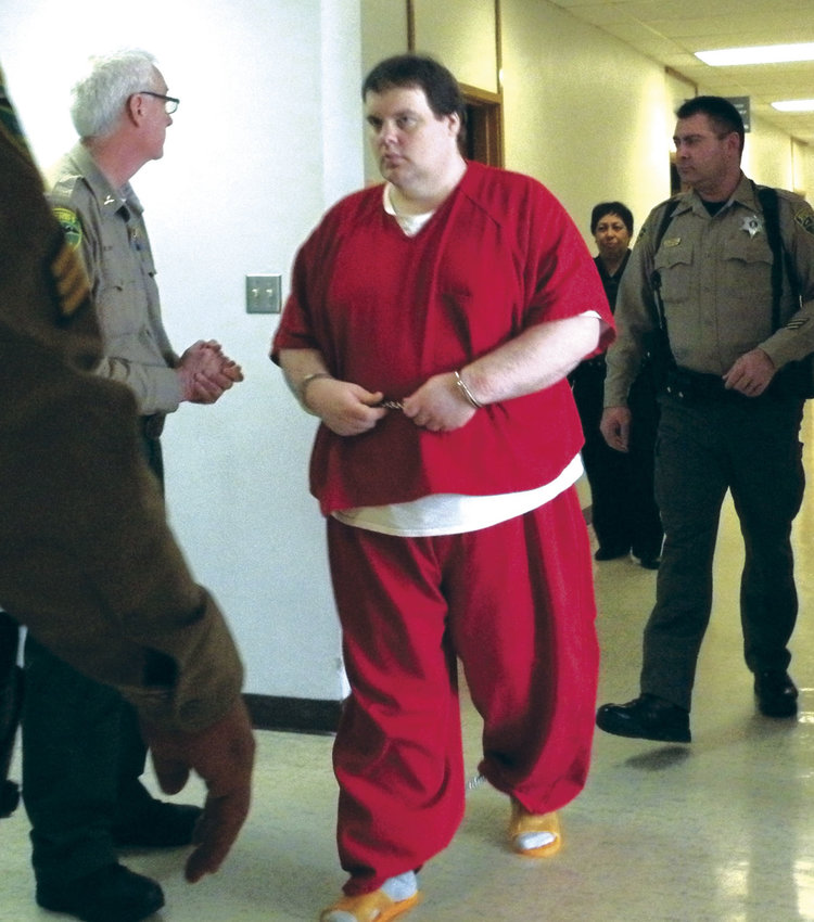 Michael J. Pierce (in red jail clothes) in the Kitsap County Courthouse in March 2014. He is serving a 117-year sentence. File photo by Allison Arthur