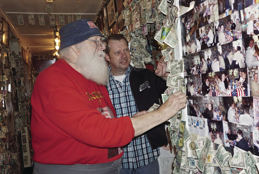 Dan McIntyre (left) who volunteers as a Toys for Tots Santa, and Fat Smitty's manager Casey Carson begin taking down money from the restaurant's walls on Saturday. Toys for Tots was one of the beneficiaries of the $26,582 taken from the walls. Photo by Charlie Bermant