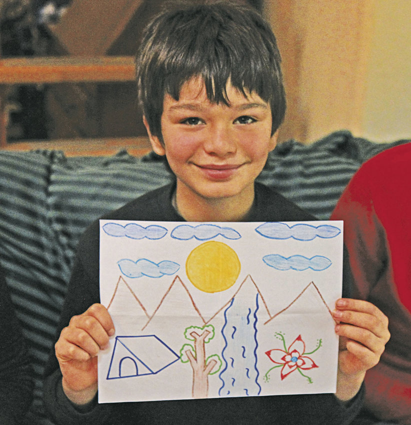Diego Garcia, 10, a student in the Chimacum School District Pi Program, holds up a drawing he received from one of 25 pen pals he has at a school in Cuba. His neighbor, Heather Harding, a tour guide, serves as a courier, bringing drawings from Garcia to Cuba and drawings from students in Cuba back to Garcia. Photo by Allison Arthur
