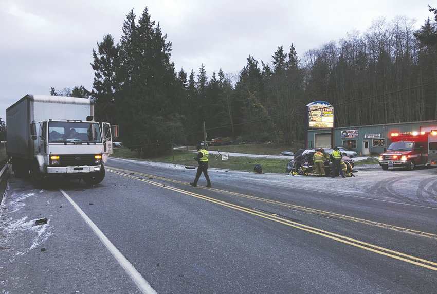 Two people in the Volkswagen Beetle (right) were injured when the VW was caught in the middle of a five-car, chain-reaction accident Dec. 17. The wreck occurred on State Route 20 just outside Port Townsend when a Jeep inbound to PT had stopped, attempting a left turn into A Plus Equipment Rental's access, according to the Washington State Patrol. The white truck (left) rear-ended the Volkswagen, causing it to rear-end one vehicle and spin into the other lane, where it struck a pickup. Photo by Bill Beezley, East Jefferson Fire Rescue