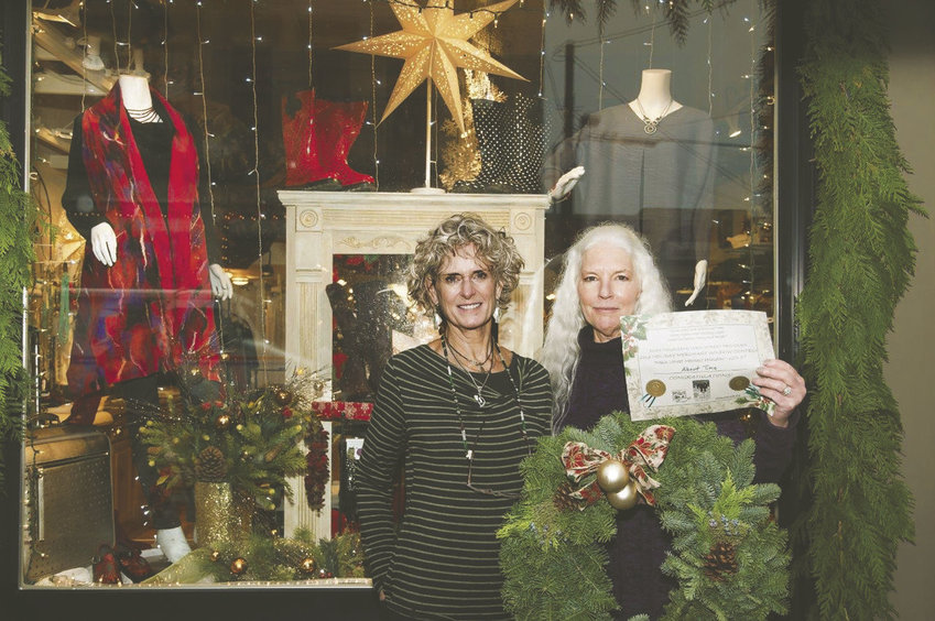 About Time at 830 Water St. won the Gold Award for its merry window display, which features a welcoming hearth showcasing holiday apparel ideas, the judges said. Pictured are staff members Jan Hopfenbeck (left) and Nancy Cherry Eifert. Photo courtesy Studio J Photography
