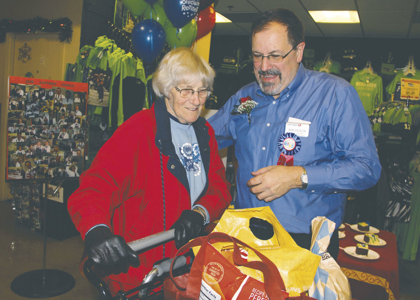 Port Townsend Safeway customer Ethel Crutcher greets Bob Giesler, store director, at a retirement party Dec. 19. Giesler, who has managed the store for 28 years, retires Dec. 23. Photo by Patrick Sullivan