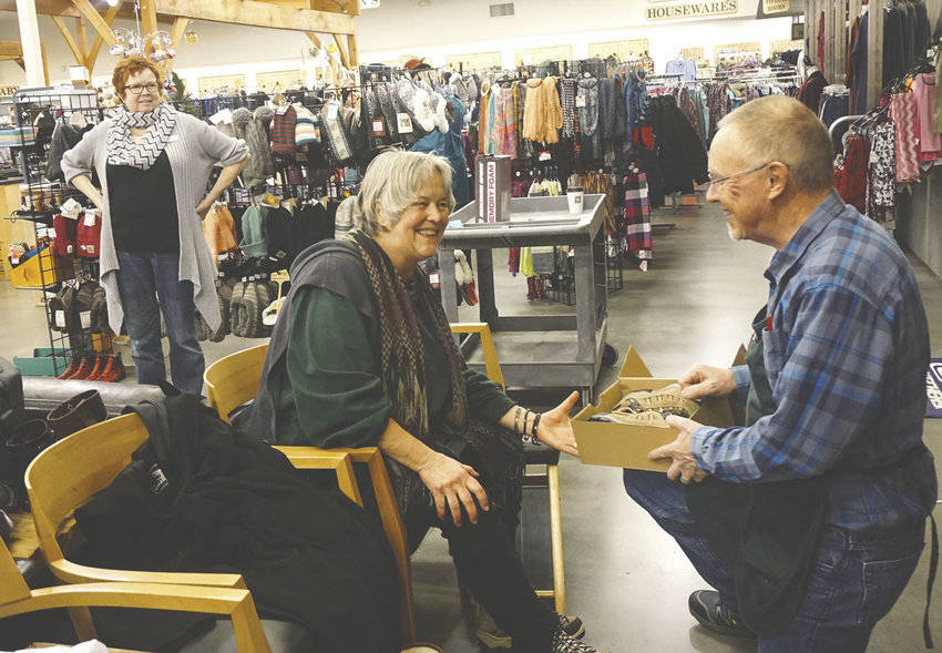 Quimper Mercantile manager Sheldon Spencer (right) helps Mary McLean with her shoe choice as employee Robbie Clay observes. Photo by Charlie Bermant