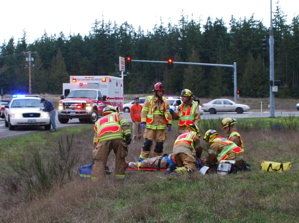 Paramedics treat a man who suffered only minor injuries after the pickup he was driving left State Route 20 and rolled three times Thursday afternoon just south of Port Townsend. Two passersby helped the man crawl from his pickup, at the time on two wheels. The 2:35 p.m. wreck snarled traffic near the SR 19 and SR 20 intersection. Photo by East Jefferson Fire Rescue