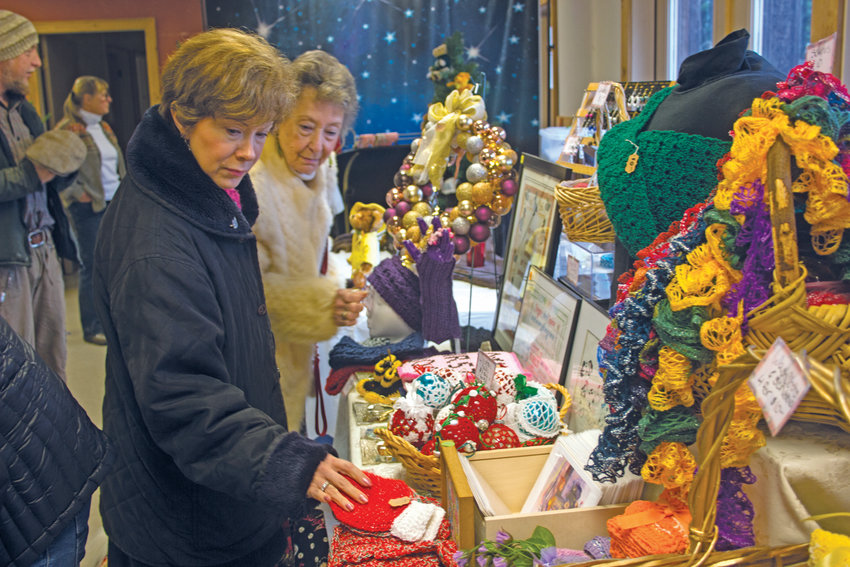 The Quilcene Holiday Craft Fair on Nov. 24 drew shoppers such as Debbie Nasser and her mother, Sharone Norwood, who browsed the eclectic selection of vendors such as Jennie Reynolds.
