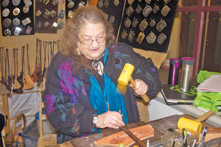Jenny Preston of Chimacum hammers elaborate patterns into the belts she fashions for her business, Snow Creek Leather, at the Port Townsend Arts Guild's Holiday Crafts Sale on Nov. 24.