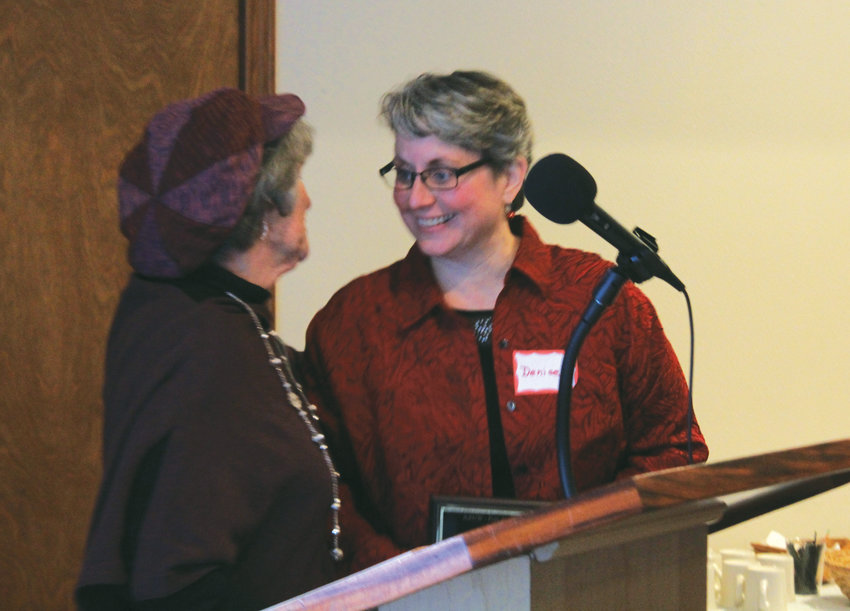 AAUW's Michael Kubek, left, presents Key City Public Theater Artistic Director Denise Winter with the Woman of Excellence award on Dec. 1.
