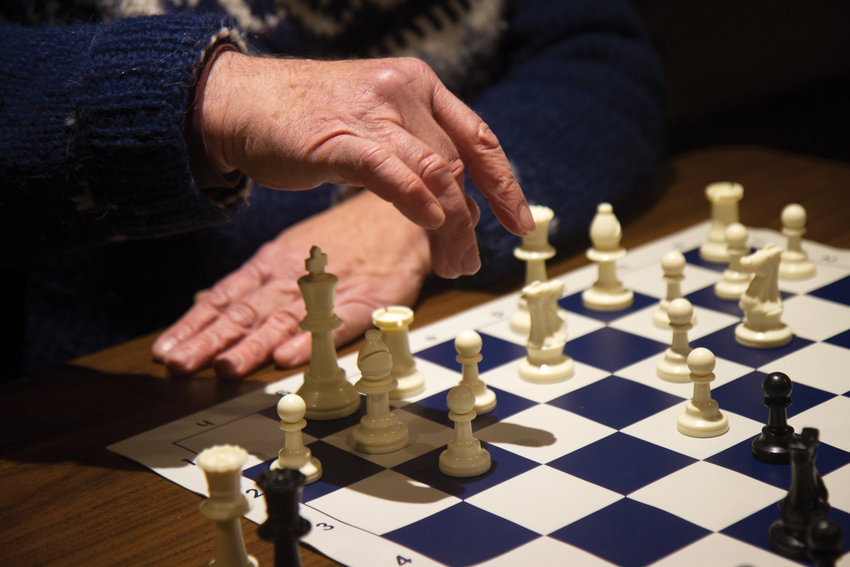 Port Townsend's Mike Murray, who has been playing chess since he was 16, reaches for a pawn during a timed match Dec. 6 at the weekly meetup of the newly formed High Tide Chess Club in the basement of the Bishop Victorian Hotel, 714 Washington St., in Port Townsend.