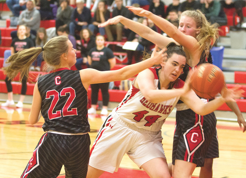 Port Townsend junior Izzy Hammett moves in the post between Crosspoint defenders Addison Schmidt, left, and Joelle Zoolkowski.