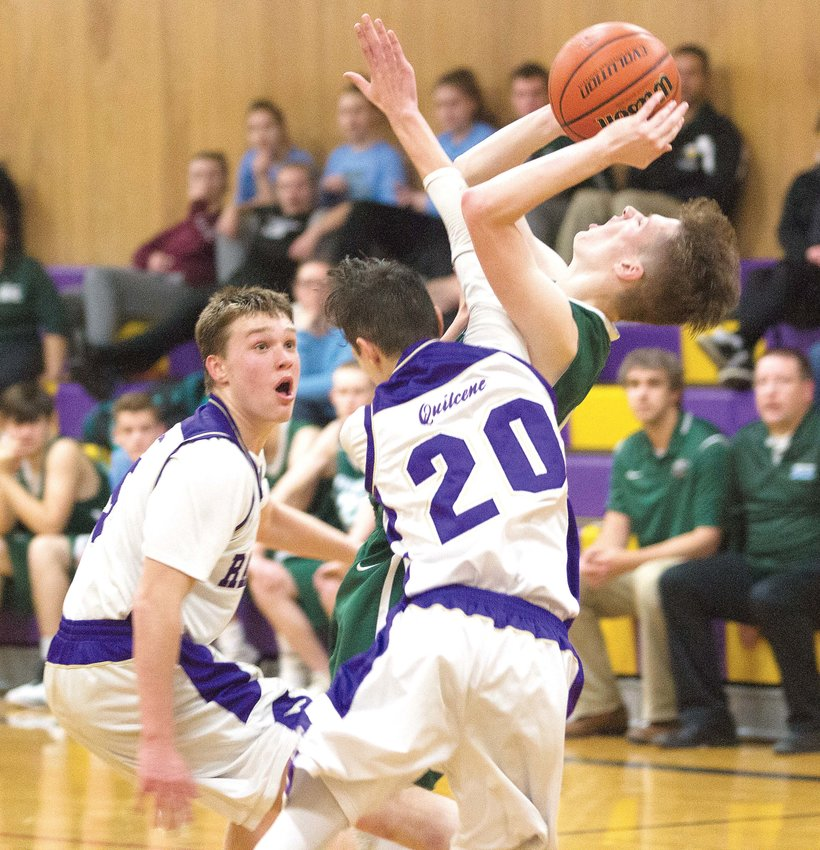 Quilcene defenders Bishop Budnek, left, and Holdem Elkins, 20, converge on Evergreen Lutheran's Brian Rittierodt in the fourth quarter of their Class 1B SeaTac League West Division contest on Dec. 13 at Quilcene High School.