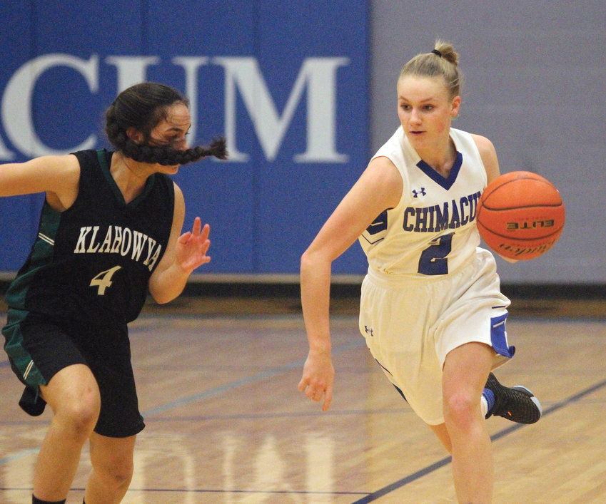 Chimacum senior guard Jada Trafton, right, leads a fast break past Klahowya junior Maile Lueck during the Cowboys' 55-35 win Jan. 11 at Chimacum High School.