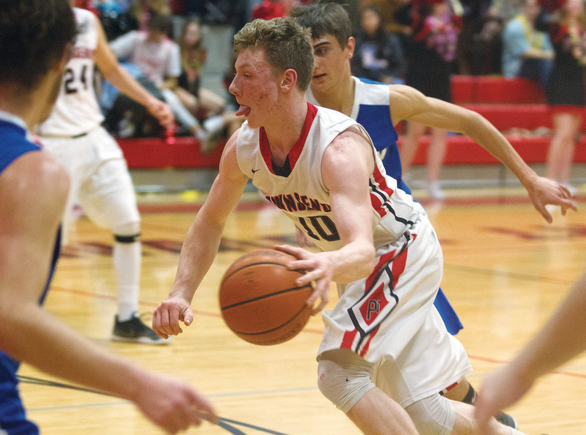 Port Townsend senior forward Cole Crawford sticks out his tongue as he drives toward the basket against the Chimacum Cowboys on Jan. 25 during the schools' Class 1A Olympic League game at Bruce Blevins Gymnasium.