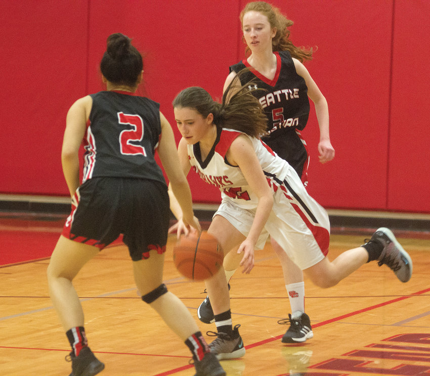 Port Townsend sophomore guard Sorina Johnston tries to maintain possession of the ball in the face of Seattle Christian defenders Ava Louie, left, and Claire Maulding.