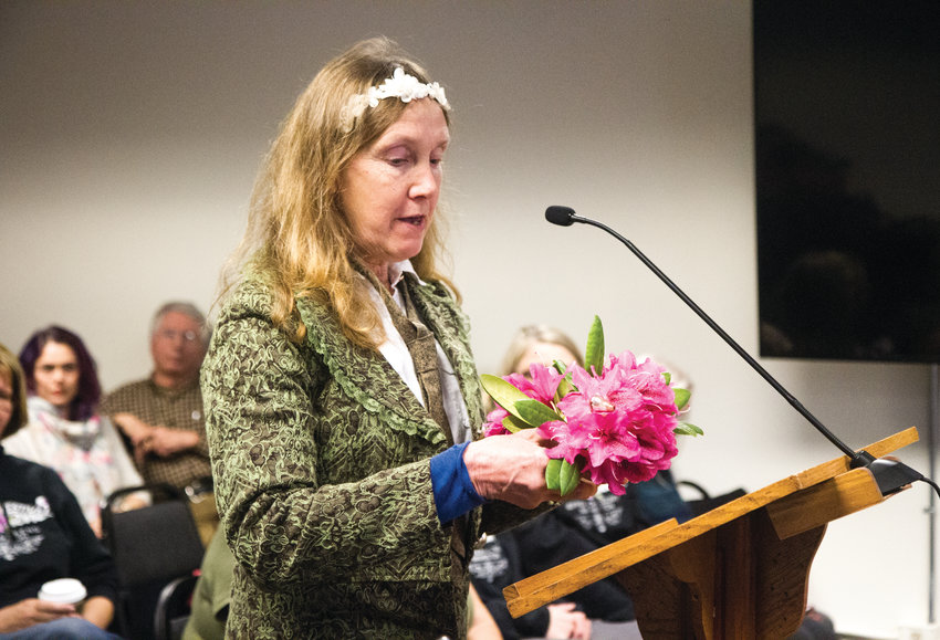 Jana Hoffman Allen presented rhododendrons to the Jefferson County Commission at its meeting Monday morning. She was one of many public speakers who asked the commissioners to help find a home for the Rhody Fest carnival, which commissioners had hoped would not be held again at Memorial Field, due to the damage it causes.