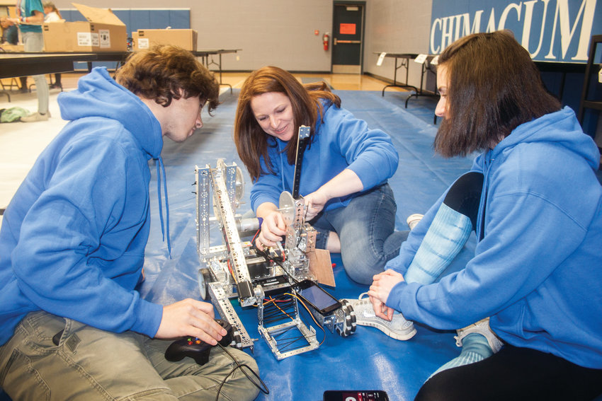 Chimacum High School junior Brend'n Blankenship, science teacher Courtney Prather and Haley Morrison assemble their robot in the CHS gymnasium April 13.