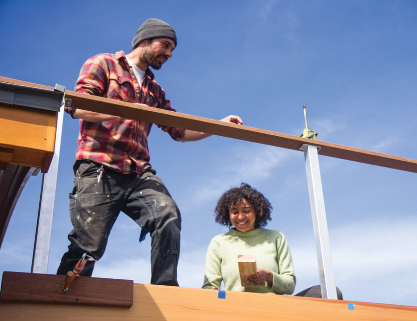 Shawn Buffer and Taylor Austin work to install the deck on top of the house boat Bella Barca.