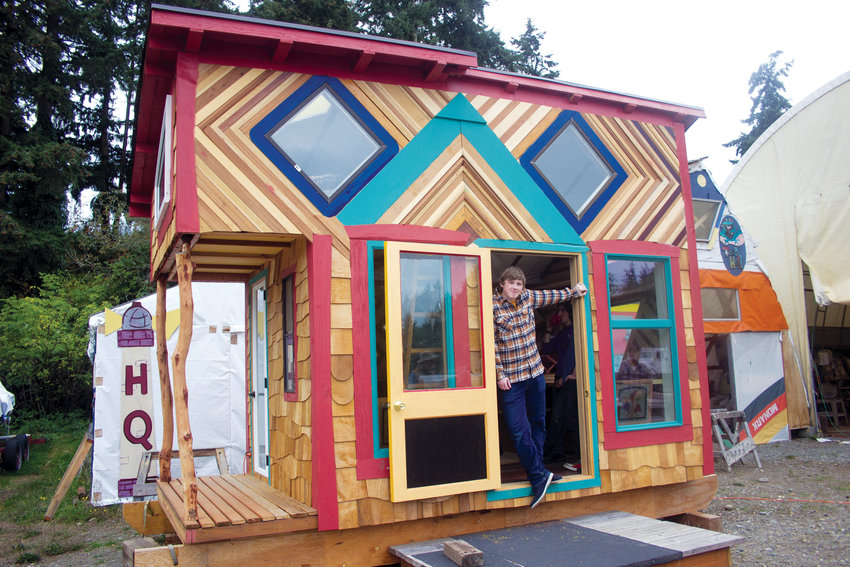 """Community Boat Project student Xander Reeves shows off the paint job he applied to the CBP's second annual """"Tiny House"""" project last fall."""